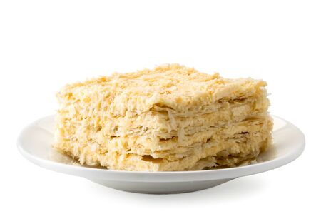 Piece of Napoleon cake in a plate on a white background, isolated.