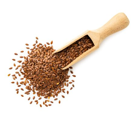 Flax seeds in a wooden scoop on a white background. The view of the top.