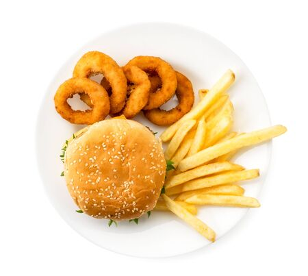 Hamburger, French fries and onion rings in a plate on a white. The view of top.
