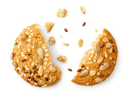 Oatmeal cookies with seeds broken in half on a white, isolated. The view of the top. Stok Fotoğraf