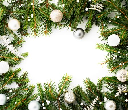 Frame of Christmas tree branches decorated with toys on a white background, a place for text. Christmas background