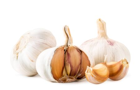 Two heads of garlic, half and slices close-up on a white background. Isolated.