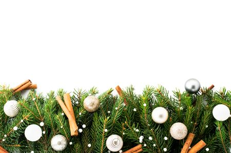 Christmas tree branches decorated with toys and cinnamon sticks on a white background, place for text. Stok Fotoğraf