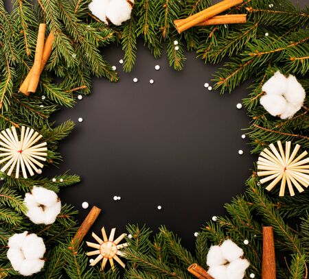 Christmas tree branches with cotton, straw snowflakes and cinnamon on a black background, place for the text. Christmas background. Stok Fotoğraf - 133347244