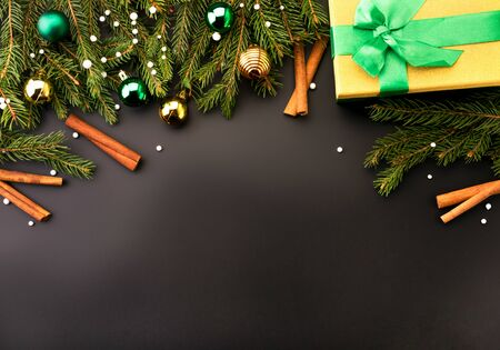 Christmas tree branches decorated toys and cinnamon sticks with gift box on a black, place for text. Christmas background. Stok Fotoğraf - 133164137