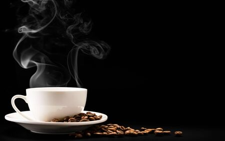 A Cup of hot coffee with steam and beans on a black background, a place for text. Stok Fotoğraf