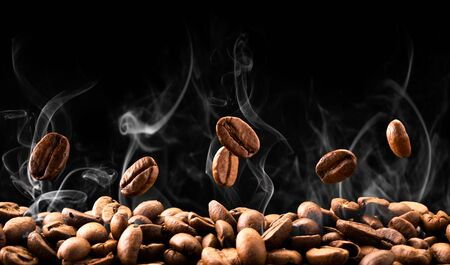 Coffee beans fall in smoke on a black background, a place for text.