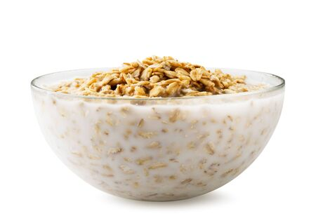 Oatmeal with milk in a glass plate on a white background. Isolated.