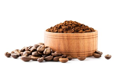 Ground coffee in a wooden plate and coffee beans on a white background, isolated.