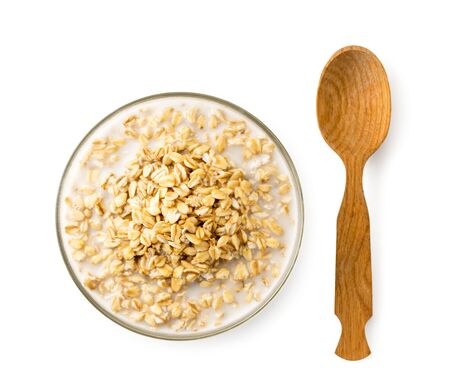 Oatmeal with milk in a plate and a wooden spoon on a white background. The view of the top. Stok Fotoğraf - 133249049