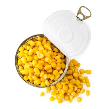 Canned corn in a jar and a scattered pile on a white. The view of the top. Banco de Imagens