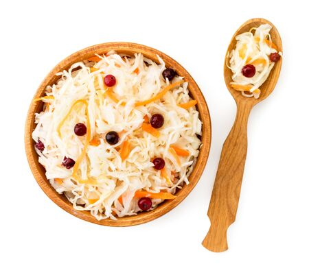 Sauerkraut with cranberries in a wooden plate and spoon on a white background. The view of the top.