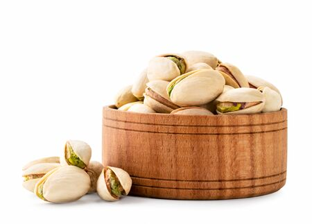 Pistachios in a wooden plate and scattered on a white. Isolated. Stok Fotoğraf