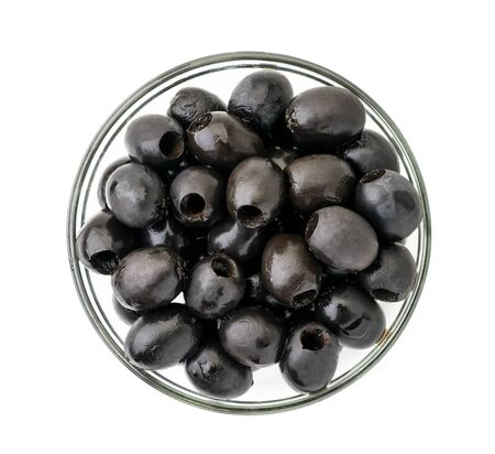 Black olives in a glass plate on a white. The view of the top.