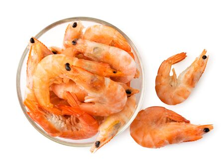 Frozen shrimp in a plate and scattered on a white. The view of the top.