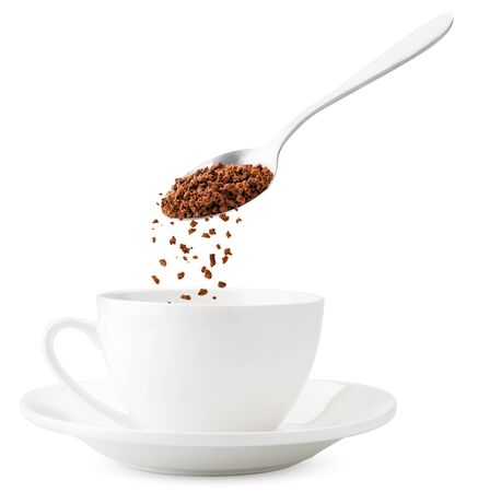 Instant coffee pours from a spoon into a Cup, close-up levitation on a white background. Making instant coffee. Isolated