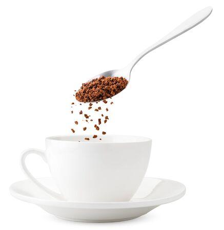 Le café instantané se déverse d'une cuillère dans une tasse, lévitation en gros plan sur fond blanc. Faire du café instantané. Isolé Banque d'images