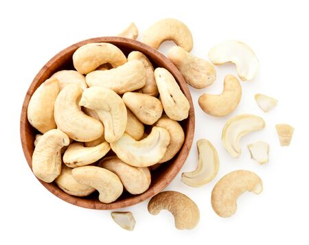 Cashew nuts in a wooden plate and scattered on a white background. View from the top Imagens