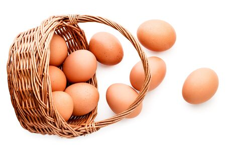 Chicken eggs spilled from the basket on a white background. The view from the top