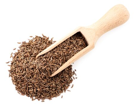 Cumin seeds in a wooden spoon on a white. The view from top