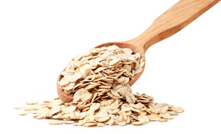 Oatmeal spills out of a wooden spoon on a white background. Isolated