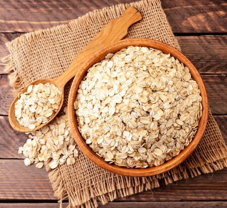Oatmeal in a plate and spoon on a wooden background. The view from top