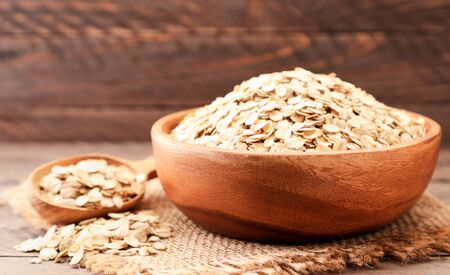 Oatmeal in a wooden plate on a brown background close-up. Food photo 스톡 콘텐츠