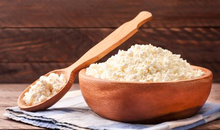 Cottage cheese in a plate and spoon with a napkin on a wooden background close-up. Food photo
