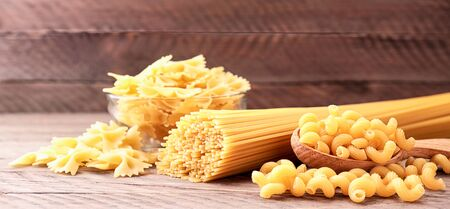 Assorted spaghetti pasta, butterflies, curls on wooden background close-up 스톡 콘텐츠