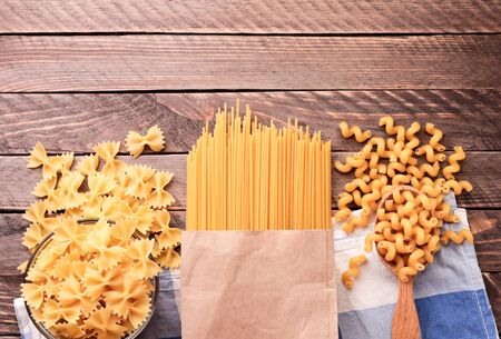 Assorted spaghetti pasta, butterflies, curls on wooden background close-up. The view from top 스톡 콘텐츠