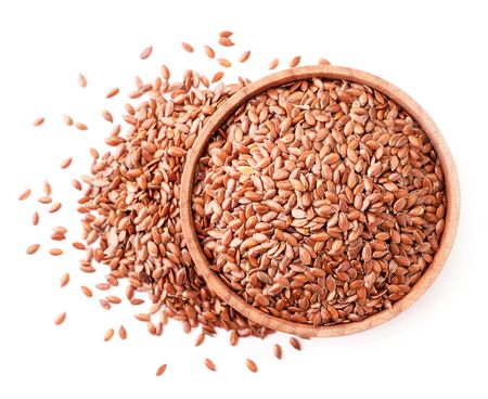Flax seeds in a wooden bowl on a white background isolated. The view from top