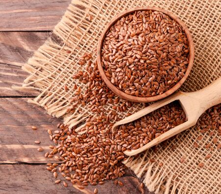Flax seeds in a wooden bowl and spatula, background. Top view