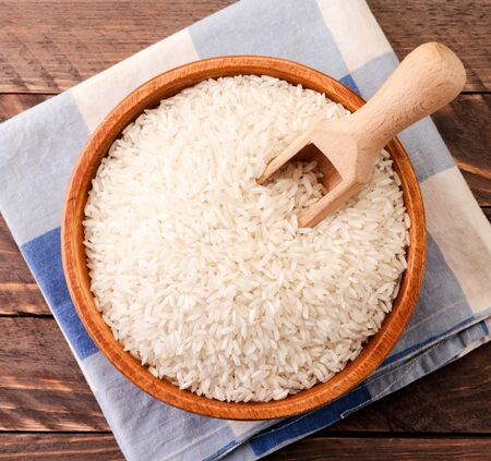 Rice in a wooden plate with a spatula, background. The view from top
