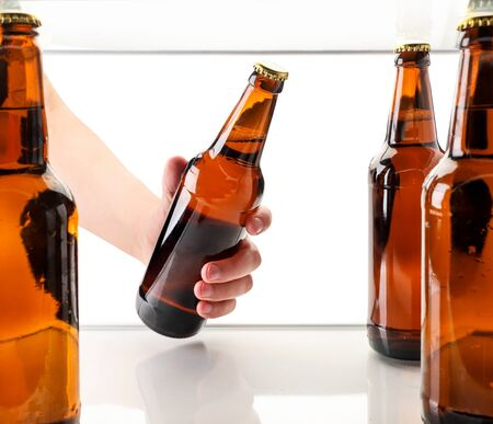 A man's hand takes out a bottle of beer from the refrigerator on a white background isolated. The view from the fridge
