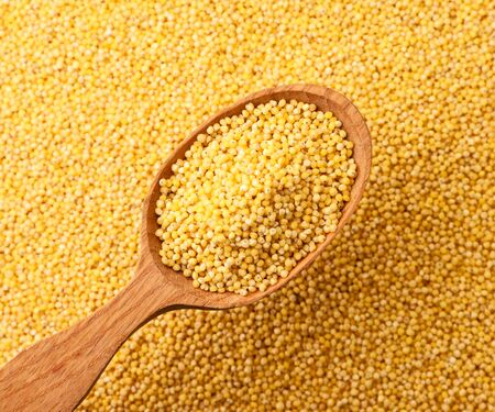 Millet in a wooden spoon close-up on a background of cereals. The view from top Stockfoto