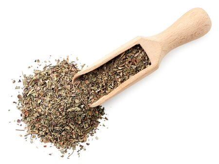 Dry basil in a spatula closeup on a white background, isolated. The view from top