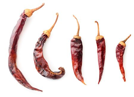 Collection of red dry chili peppers close-up on a white background. The view from top