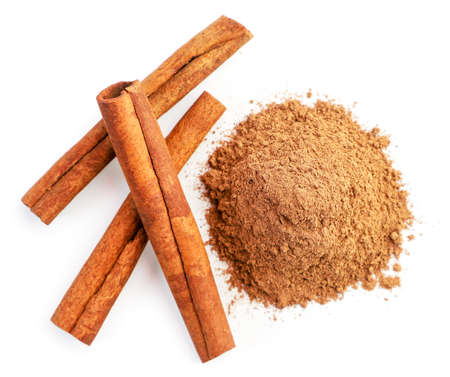 Cinnamon sticks and ground close-up on white background, isolated. The view from top