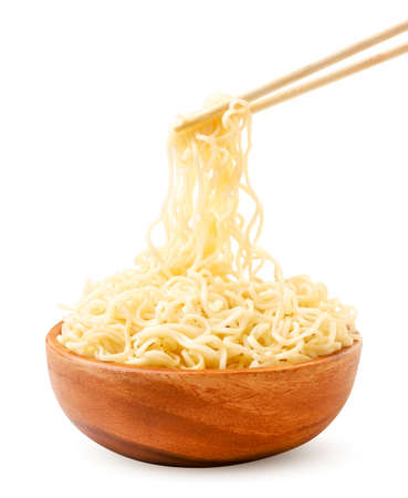 Noodles in a wooden bowl and chopsticks close-up on a white plate. Isolated