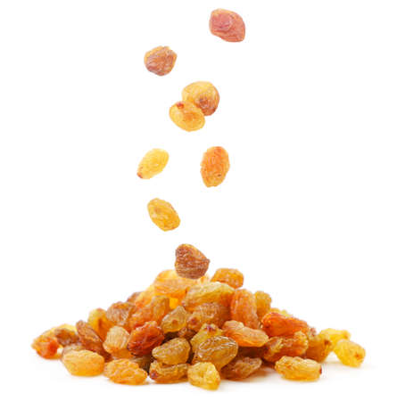 Raisins falls on a pile of close up on a white background. Isolated