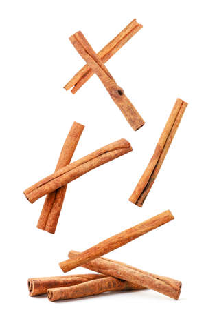Cinnamon sticks fly and fall on a heap on a white background. Isolated
