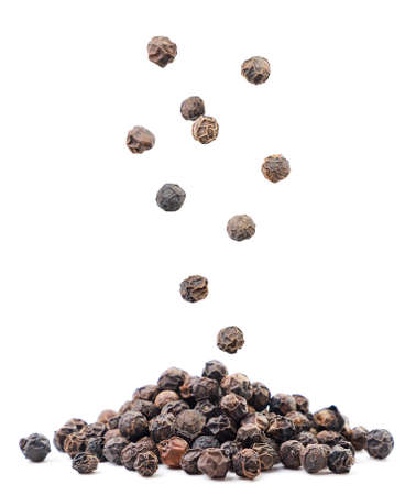 Black peppercorns falling on a pile on a white background. Isolated Stok Fotoğraf