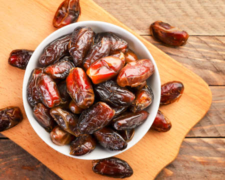 Dates fruit in a plate on a wooden background. The view from top Stok Fotoğraf