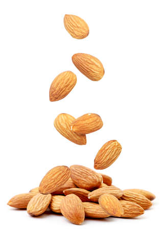 Almond nut flies and falls on a heap on a white background. Isolated Stok Fotoğraf