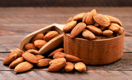 Almond nuts in a plate on a wooden background Stok Fotoğraf