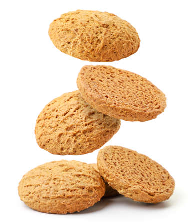 Oatmeal cookies flies and falls on a pile close-up on a white background, levitating cookies. Isolated