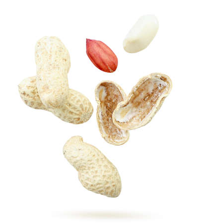 Peanuts in shell, whole and chopped close-up flies on a white background. Isolated
