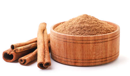 Cinnamon sticks and cinnamon powder in a plate close-up on a white background. Isolated