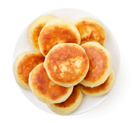 Fried cheese pancake in plate close up on white background, isolated. The view from top