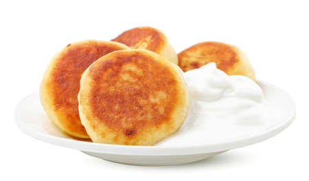 Cheese pancake in a plate with sour cream close-up on a white background. Isolated